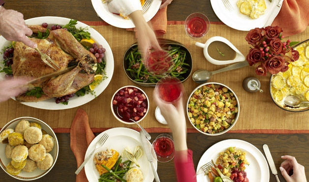 Table set for Thanksgiving with hands passing glasses across the table